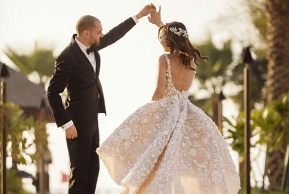 Husband spinning his wife during their Wedding dance